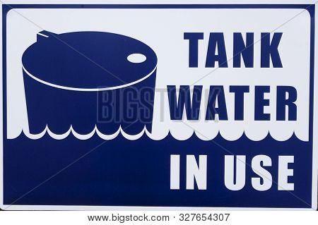 Tank Water In Use Sign At A Suburban House.