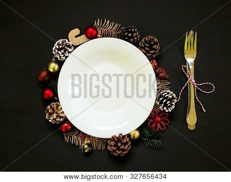 Chirstmas Wreath Decoration, Empty White Plate. Flat Lay, Top View. Black Background. Copy Space.