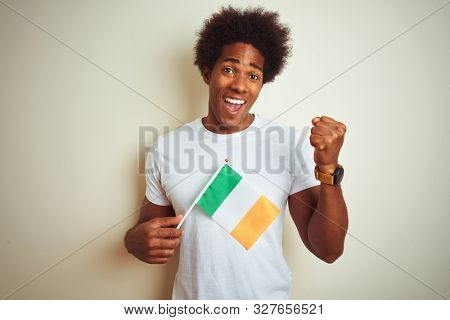 Young african american man holding Ireland Irish flag standing over isolated white background screaming proud and celebrating victory and success very excited, cheering emotion