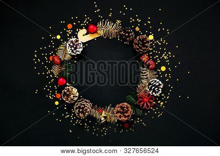 Chirstmas Wreath Decoration. Flat Lay, Top View. Black Background. Golden Confetti. Copy Space.