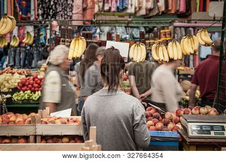 Subotica, Serbia - July 1, 2018: Young Woman Selling Bananas And Peaches On Subotica Buvljak Green M