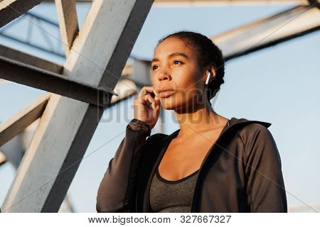 Photo of african american attractive woman in sportswear using earpods while working out on old bridge