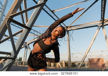 Photo of african american young woman in sportswear using earpods and stretching her body while working out on old bridge