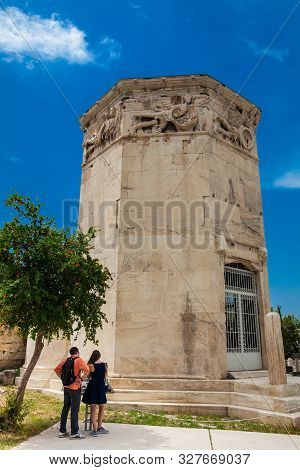 Athens, Greece - April, 2018: Young Couple Of Tourists Visiting The Tower Of The Winds Or The Horolo