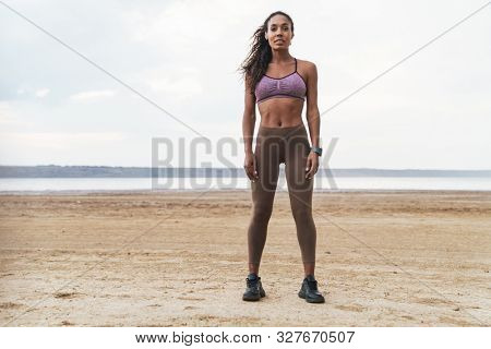 Attractive young african fitness woman standing at the beach