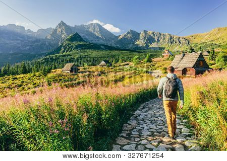 Man walking on hiking trail in Tatra mountains in Poland. Dolina Gasienicowa valley