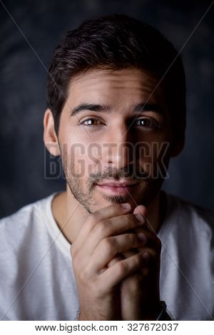 Close-up portrait of a handsome young man wearing white t-shirt. Studio shot. Men's beauty and health.