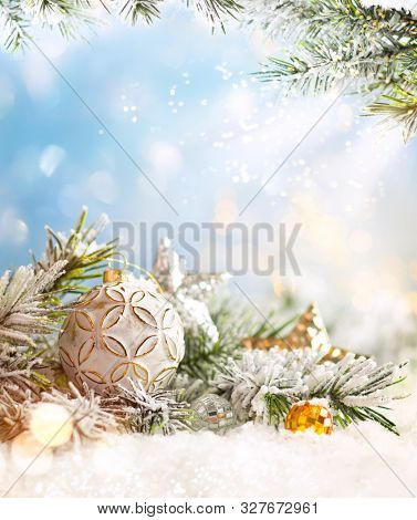 Christmas winter background with Christmas baubles and fir tree branches on snow.