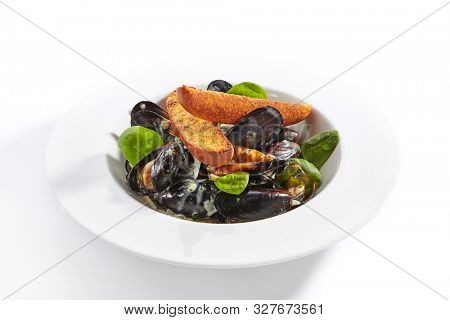 Mussel in white wine sauce closeup. Seafood with crunchy baguette slices in plate. Marine food with roasted bread and basil leaves meal ingredients. French dish isolated on white background