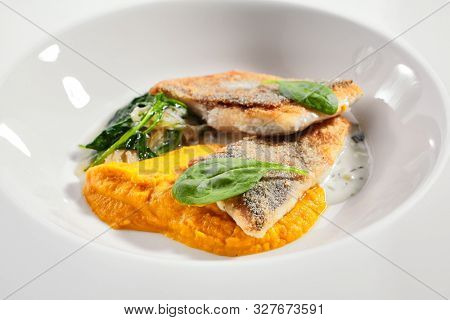 Cod fillet with pumpkin puree and spinach closeup. Seafood restaurant menu item. Delicious healthy food. Exquisite dish isolated on white background. Gourmet meal, tasty lunch close up