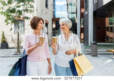 sale, consumerism and people concept - two senior women or friends with shopping bags drinking takeaway coffee on tallinn city street