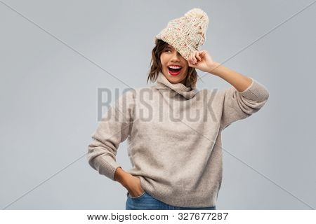 christmas, season and people concept - happy smiling young woman in knitted winter hat and sweater over grey background