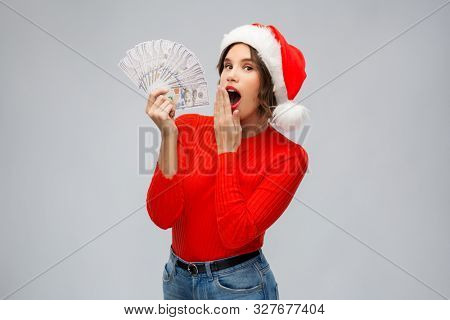 christmas, holidays and finance concept - surprised young woman in santa helper hat holding dollar money banknotes over grey background