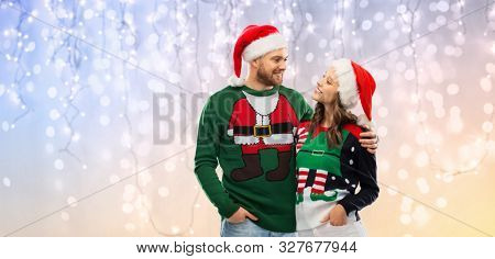christmas, people and holidays concept - portrait of happy couple in santa hats at ugly sweater party over festive lights background