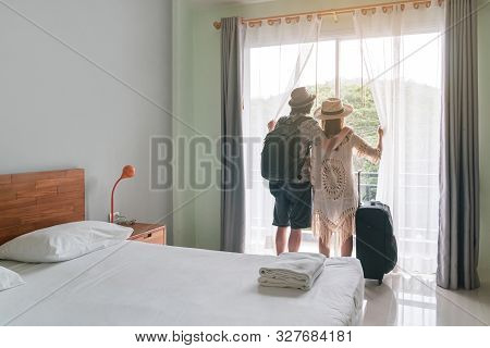 Young Couple Traveler With Luggage Looking At View In Hotel Room On Summer Vacation