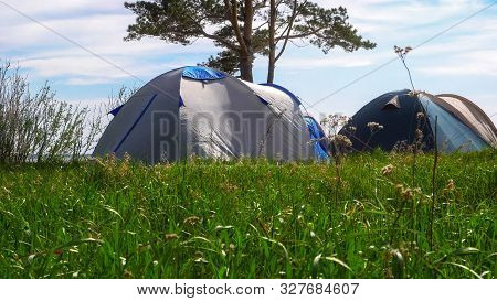 A Tent Camp By The Sea On A Meadow Of Green Grass. The Concept Of A Pleasant Family Holiday.
