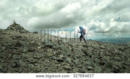 Ultra Trail Runner Climbing A Stone Trail To The Mountain Top. A Challenge To Human Strength And Abi