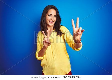 Young beautiful woman wearing yellow t-shirt standing over blue isolated background smiling looking to the camera showing fingers doing victory sign. Number two.