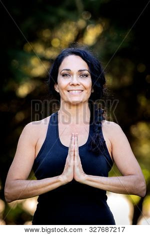 Brunette woman doing yoga during a beautiful day in a park