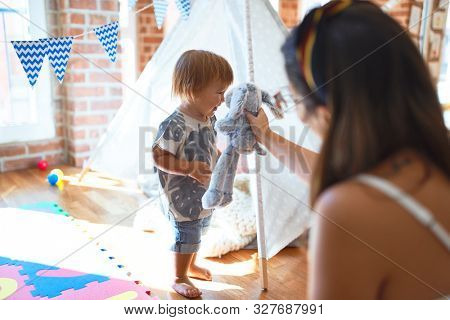 Beautiful teacher and toddler playing with elephant doll around lots of toys at kindergarten