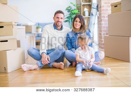 Beautiful family sitting on the floor playing with his kid at new home around cardboard boxes