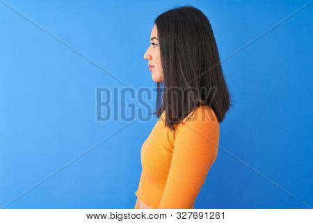 Young beautiful chinese woman wearing orange t-shirt standing over isolated blue background looking to side, relax profile pose with natural face with confident smile.