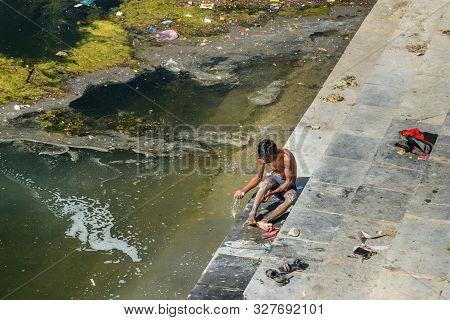 Udaipur, India - February 17, 2019: Indian Boy Washing In The Lake Swaroop Sagar Lake In Udaipur. Ra