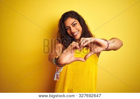 Young beautiful woman wearing t-shirt standing over isolated yellow background smiling in love showing heart symbol and shape with hands. Romantic concept.