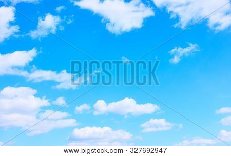 Light blue sky with white clouds -  background with space for your own text