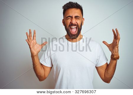Young indian man wearing t-shirt standing over isolated white background celebrating mad and crazy for success with arms raised and closed eyes screaming excited. Winner concept
