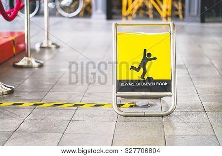 Yellow Beware Of Uneven Floor Sign Board On Tile Floor
