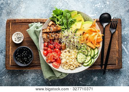 Buddha Bowl With Tofu, Avocado, Bulgur Grains, Cucumber, Carrot And Tomato Garnished With Seeds And