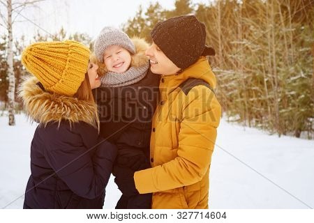 Portrait Of Happy Family In Winter Day. Mom And Dad Are Cuddling And Kissing Their Little Son In Win