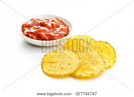 Round corn nacho chips and tomato dip. Yellow tortilla chips and salsa isolated on white background.