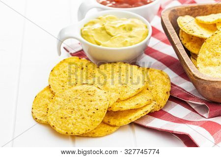 Round nacho chips and avocado dip. Yellow tortilla chips and guacamole in bowl on white table.