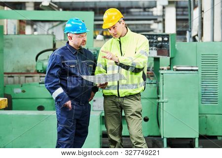 engineer and worker at industrial factory. Metal machining and manufacturing