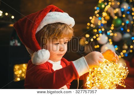 Child With Garland Lights At Christmas Tree And Fireplace On Xmas Eve. It Is Miracle. Family With Ki