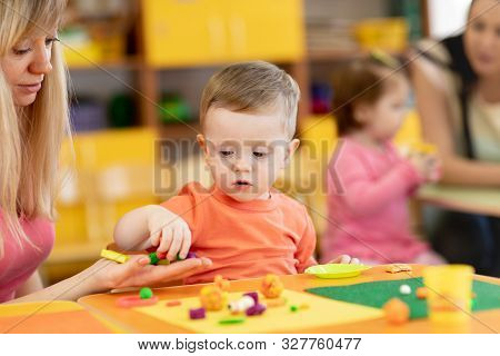 Little Kid Boy Learning To Use Colorful Play Clay In Kindergarten. Babies Group Studying In Creche O