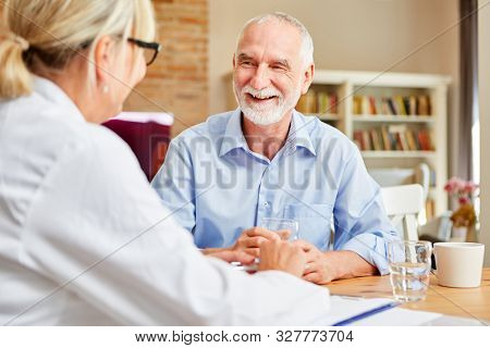 Happy senior as a patient in conversation with a female doctor during home visit