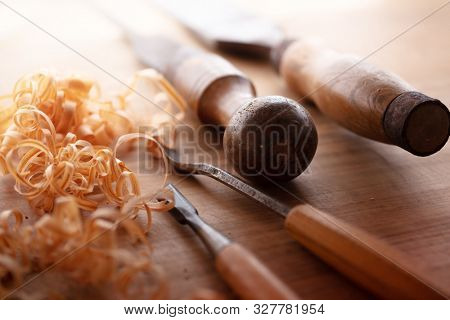 Wood working desk. beautiful wood shavings and hand tools on an old wood working desk with soft incoming light.