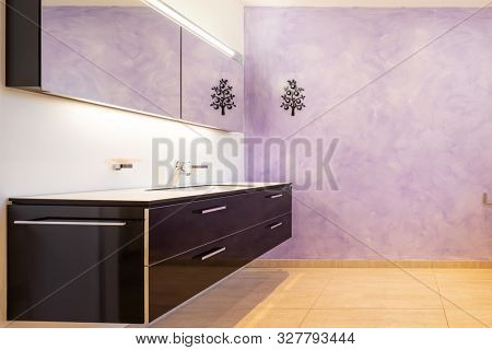 Bathroom with modern black sink and lilac wall. Nobody inside