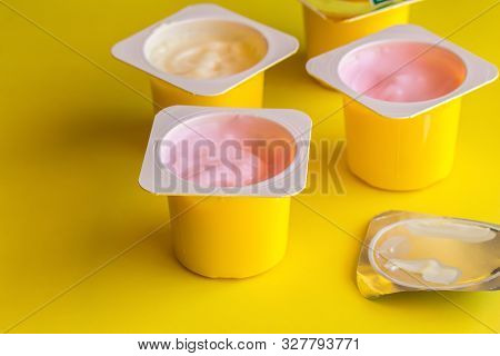 Fruit Flavoured Yogurt In Yellow Plastic Cups On Bright Yellow Background With Silver Foil Lid - Yog