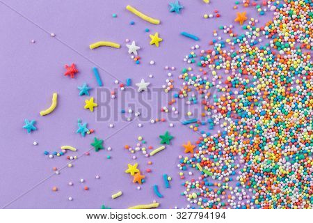 Sprinkles On Purple Background - Cake Topping Sprinkles Sprayed On Lilac Background - Top View