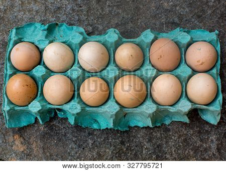 One Dozen Unwashed Chicken Eggs In Open Carton Blue Cartoon On A Rock Top View Close-up