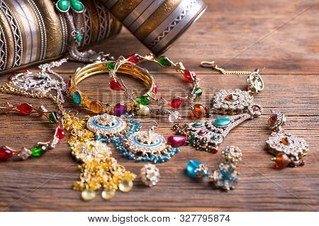 Beautiful Jewelry Close-up. Bracelets, Pendants And Earrings On The Table. A Collection Of Jewelry.