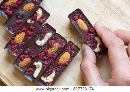 Men Hand Take Healthy Homemade Recipe Chocolate Sticks With Almonds, Cashews And Raspberries, Lie On