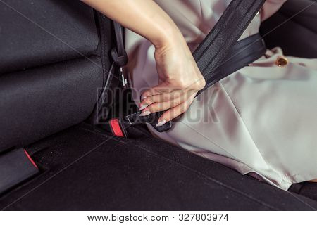 Close-up Woman In Strict Pink Suit Fastens Her Seat Belt On Passenger Seat. Safety On Road Driving C