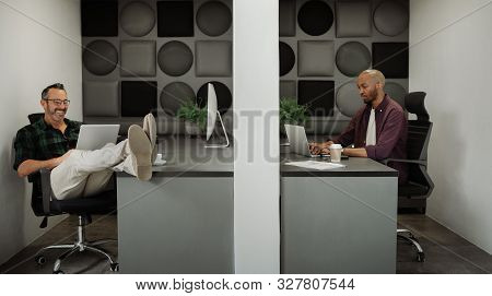 Two business entrepreneurs working in cubicle workstations in coworking office space poster