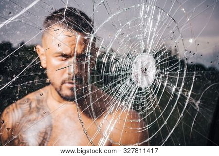 Macho Man Glasscutter Behind Crushed Glass. Sexy Hispanic Man Broken Mirror. Bullet Hole In Glass. B