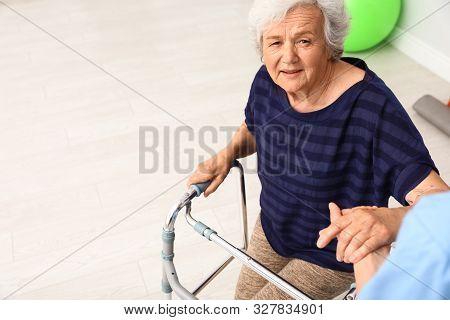 Caretaker Helping Elderly Woman With Walking Frame Indoors